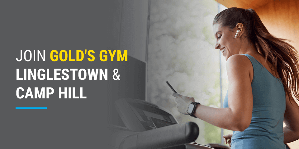 A woman checks her phone on the treadmill at her gym