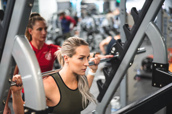 personal trainer working with gym member